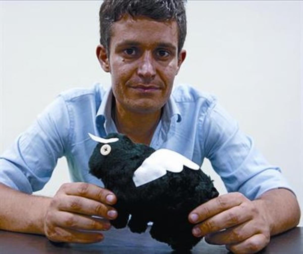 Leonardo Anselmi sostiene un toro alado de peluche.