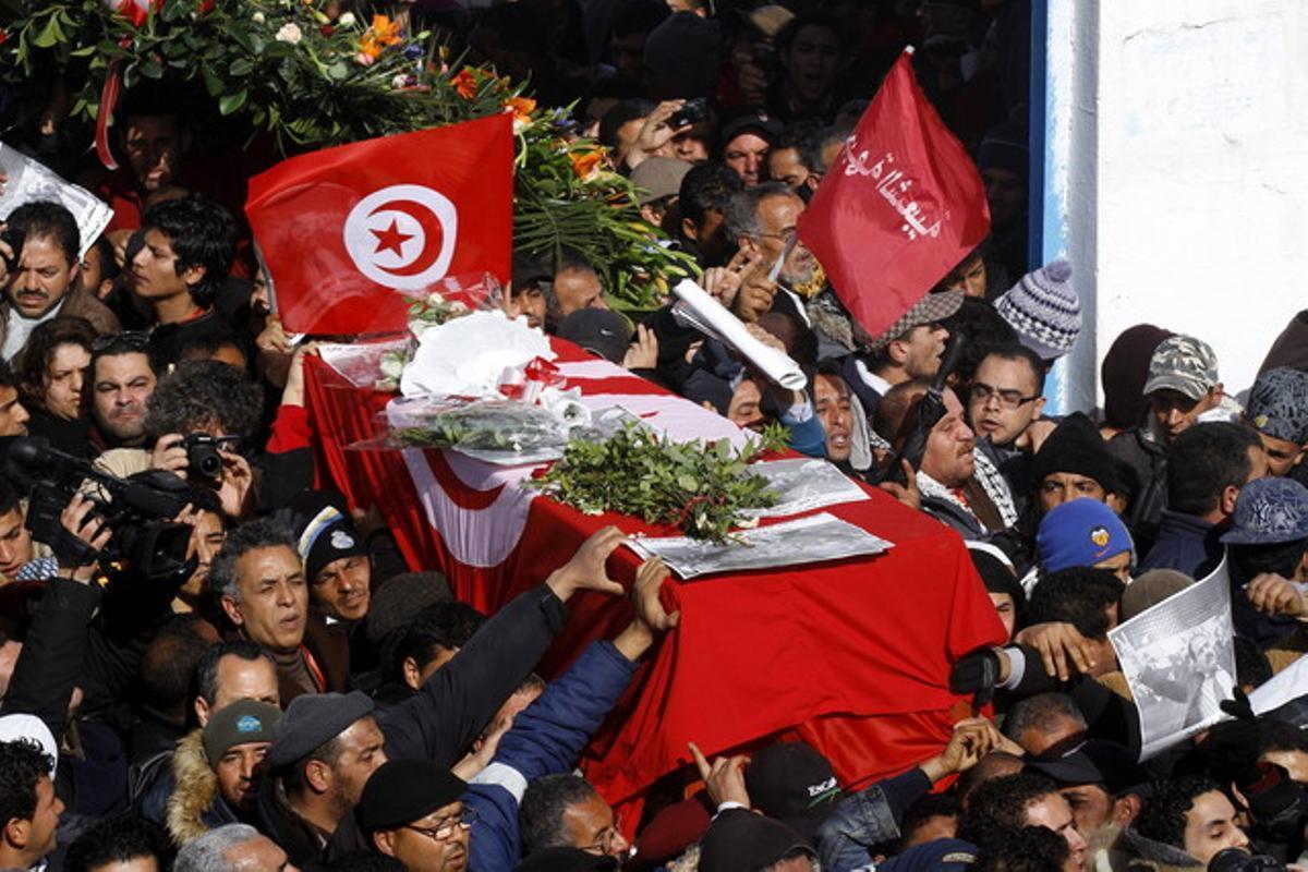Tunecinos portan el ataúd con los restos mortales del opositor Chukri Bel Aid durante su multitudinario funeral en la capital tunecina, el viernes.