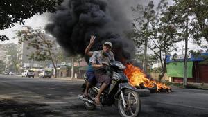 Dos ciudadanos birmanos huyen en moto de la represión en Rangún.