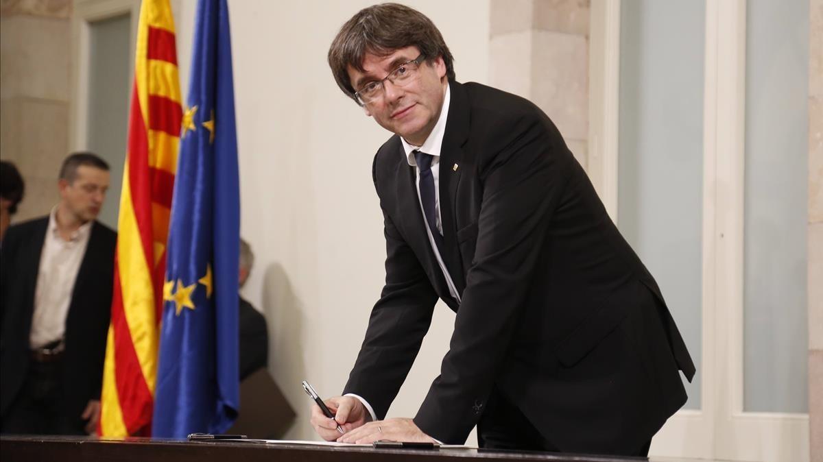 El president Carles Puigdemont en el momento de firmar la declaración, tras el pleno.