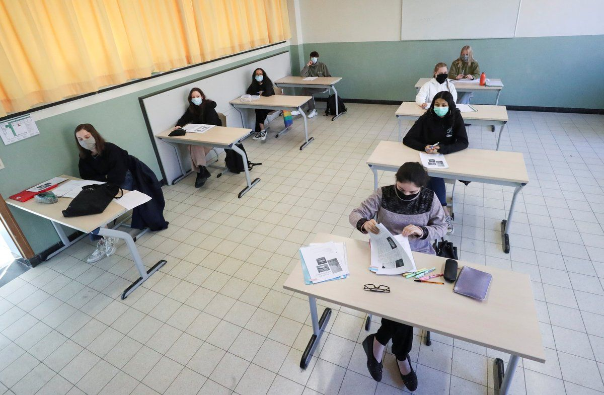 Students wearing protective face masks sit in a classroom at a flemish secondary school during its reopening in Brussels, as a small part of Belgian children head back to their schools with new rules and social distancing measures, during the outbreak of the coronavirus disease (COVID-19), in Brussels, Belgium, May 15, 2020. REUTERS/Yves Herman