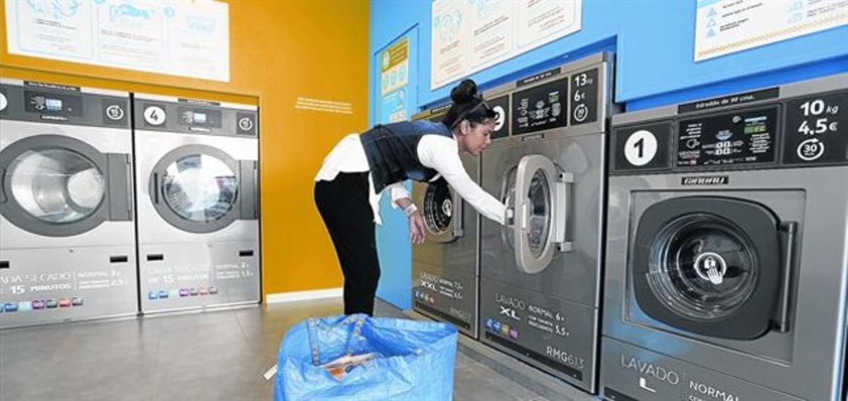 Una clienta mete la ropa en la lavadora de un autoservicio del barrio de Horta.