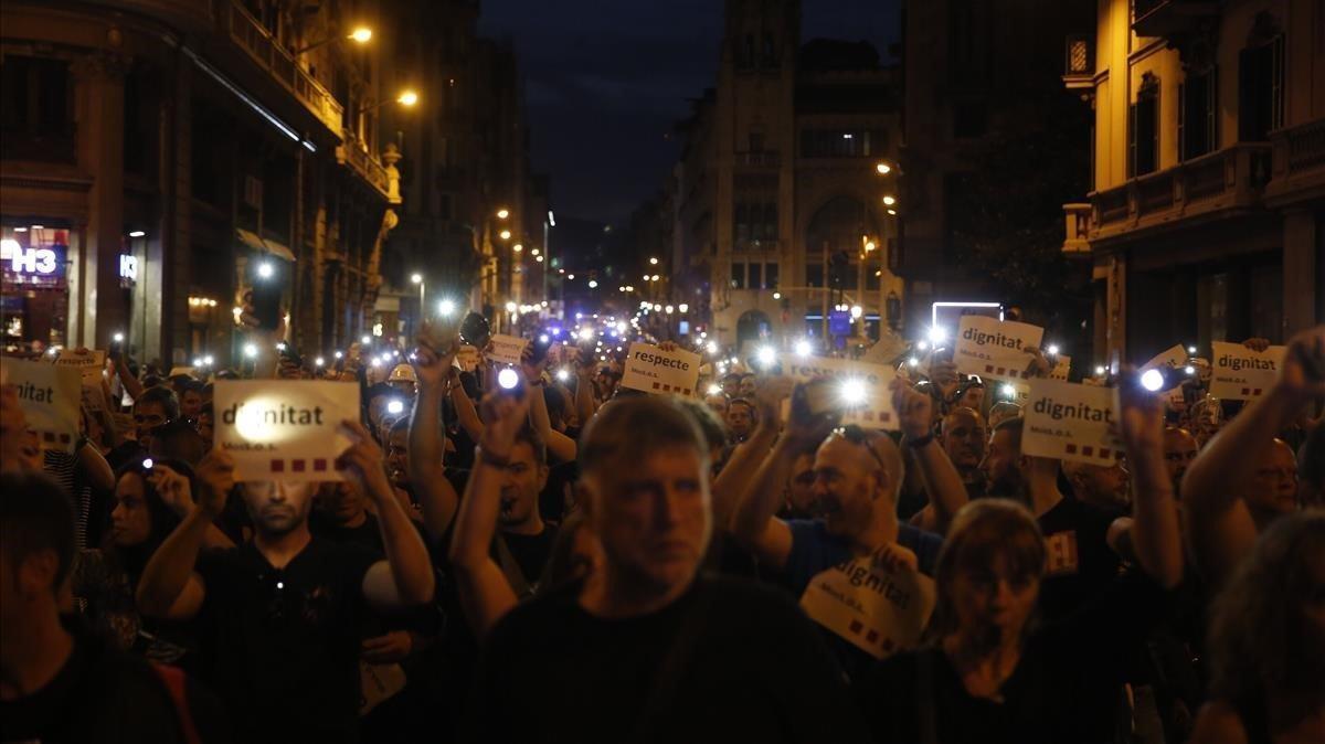 Agentes de los Mossos levantan su teléfono móvil cuando la marcha se acerca a la plaza de Sant Jaume.
