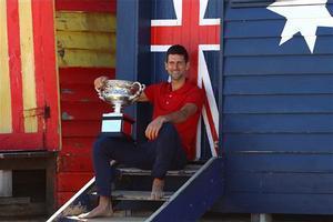 Djokovic, con su trofeo, en una caseta de playa en Melbourne.