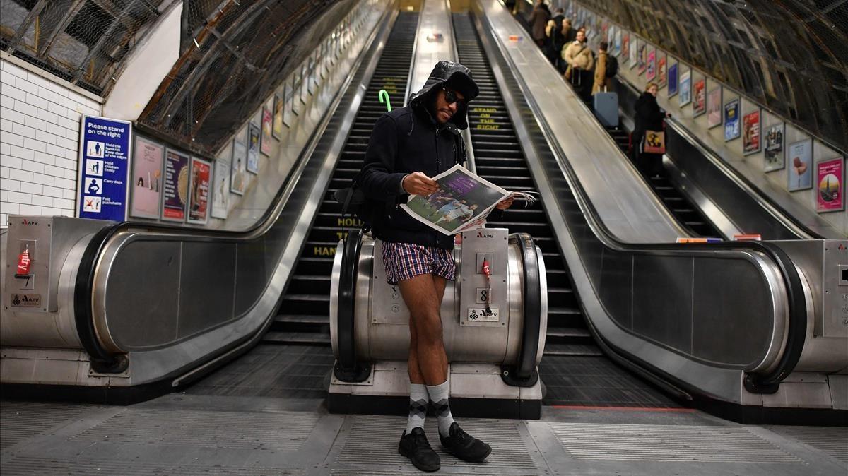 Una persona lee el diario, sin pantalones, en laestación de Liverpool Street.