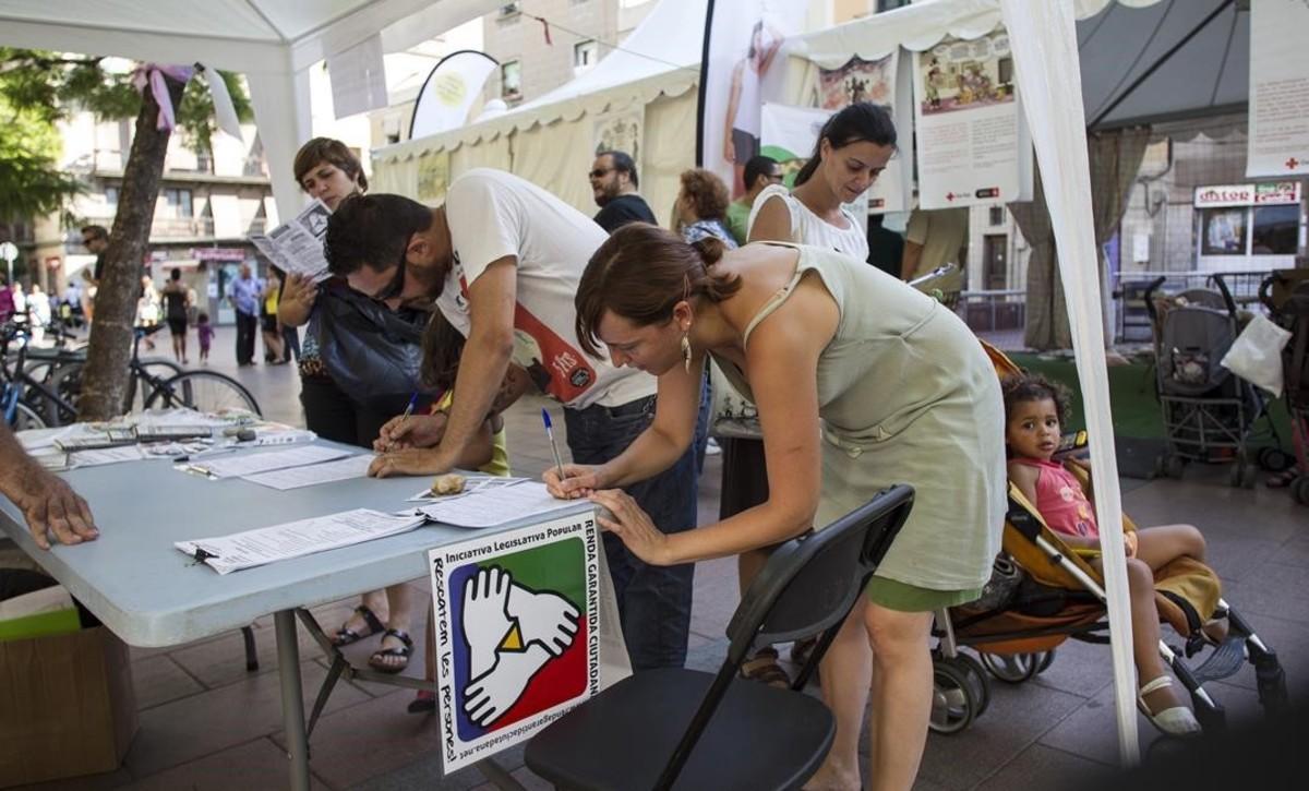 Recogida de firmas para reclamar la Renta Garantizada, en el distrito de Gràcia de Barcelona.