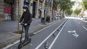 Un hombre circula en patinete por la calle de Consell de Cent, en Barcelona.