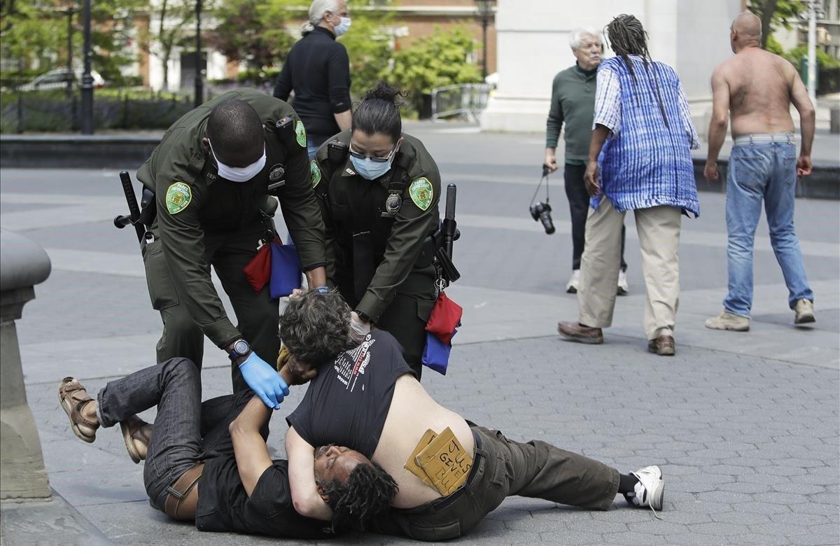 Agentes de la policía separan a los dos individuos que se peleaban en el parque Washington Square.
