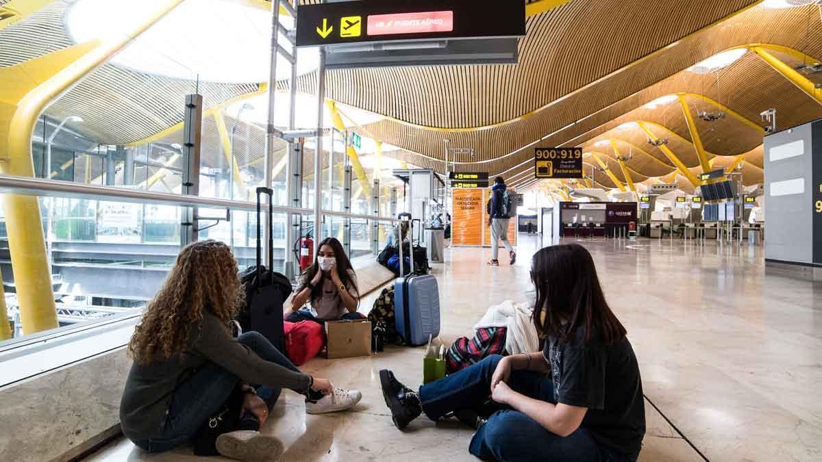 Jóvenes esperan su vuelo en el aeropuerto de Barajas.