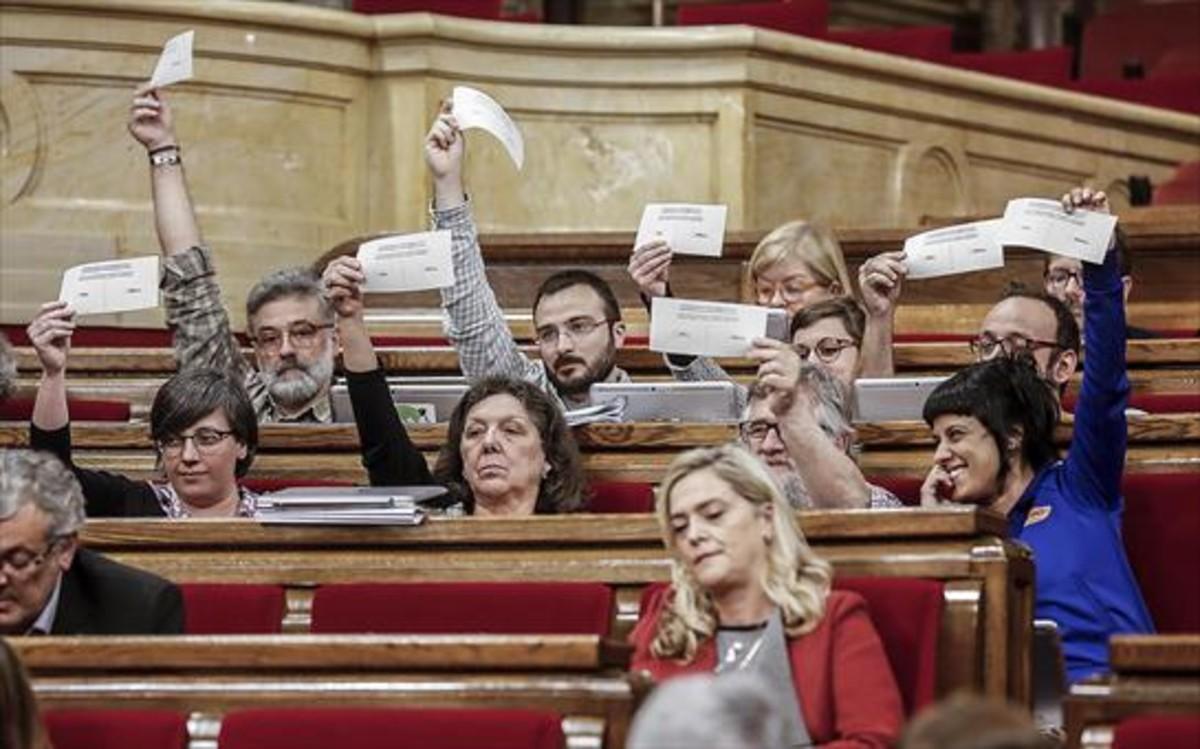 Los diputados de la CUP exhiben papeletas del eventual referéndum, ayer, en el debate del Parlament sobre los presupuestos.