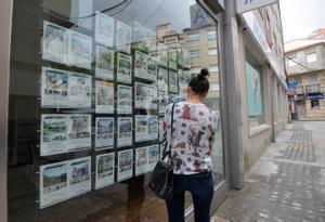 Una mujer pasa ante el escaparate de una inmobiliaria en Barcelona.
