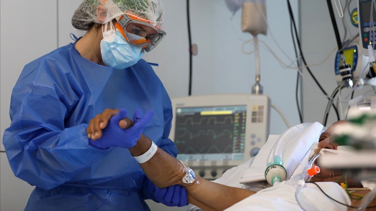 Una sanitaria atiende a un paciente en la uci del Hospital Clínic.