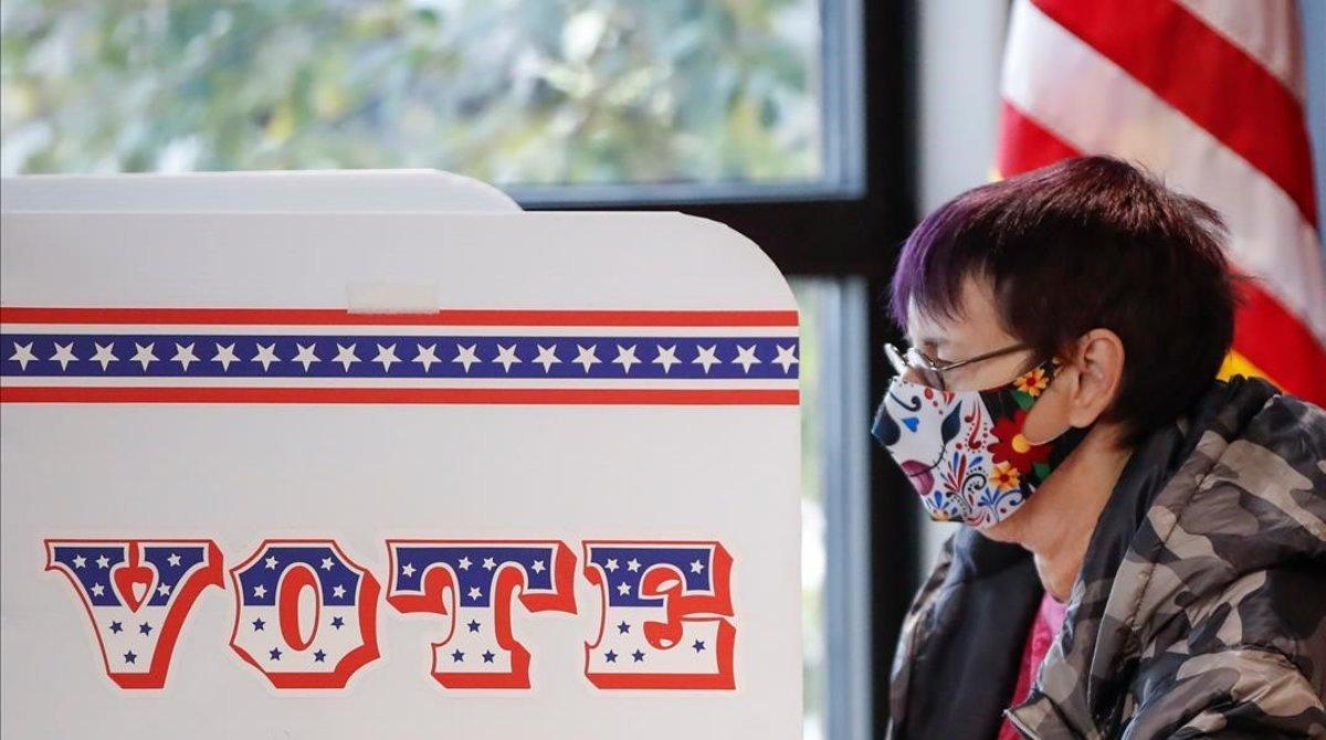 Una mujer deposita su voto en Wisconsin.