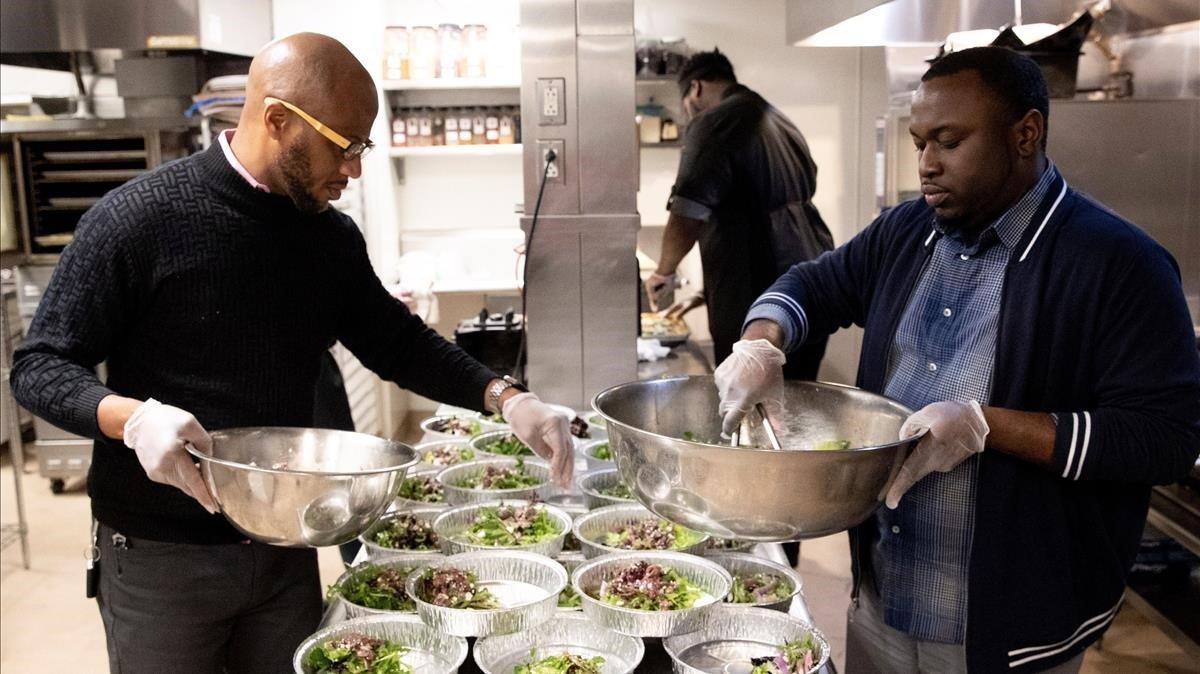 El administrador del restaurante The Grill,Joe-Jo Jennings, y el de Succotash,Demitian Gilbert (d),ayudan a preparar cajas con comida para desempleados del sector de hoteles y restaurantesen Washington.