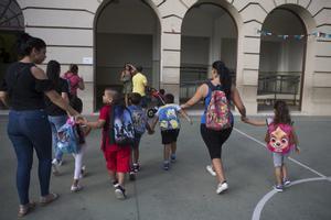 Unas madres acompañan a sus hijos al colegio.