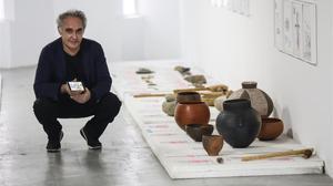 Ferran Adrià sostiene un móvil con la 'app' Tu cuento en la cocina, junto a objetos de cocina del Neolítico, en el BulliLab.