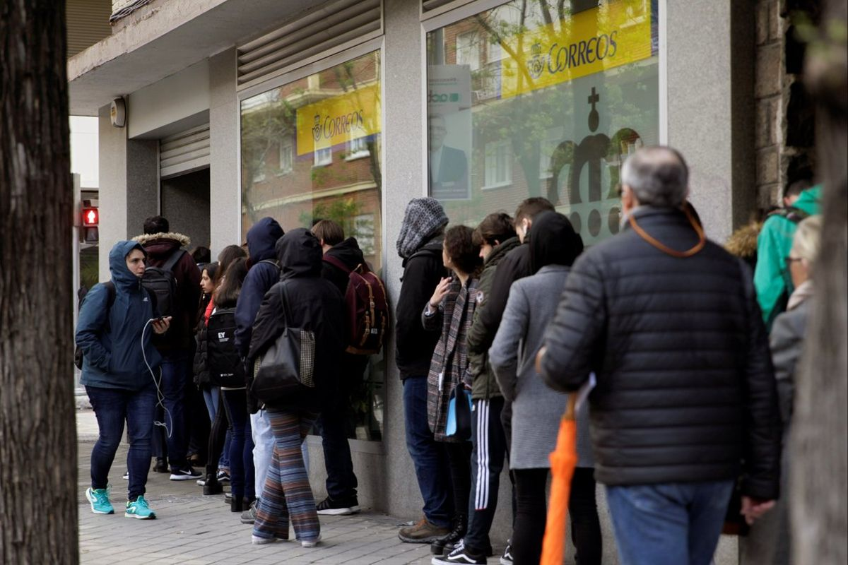 Decenas de personas hacen cola en una oficina de Correos para votar en las elecciones generales.