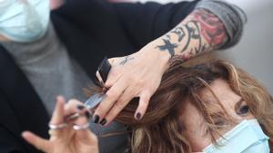 Una peluquera corta el pelo a una mujer.