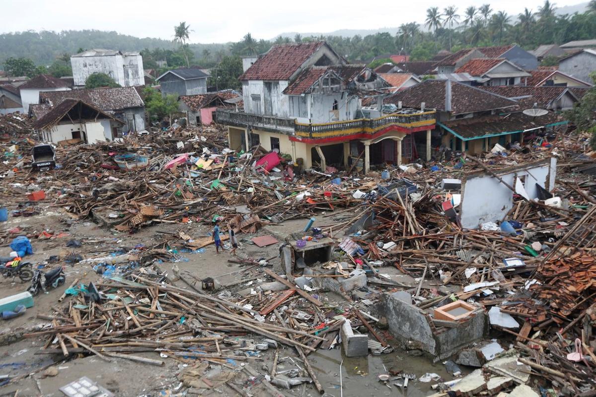 Los residentes locales caminan entre los escombros en un area devastada despues de que un tsunami golpeo el Estrecho de Sunda en SumurBantenIndonesia.EFE ADI WEDA