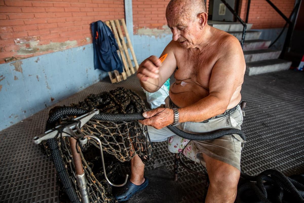 Un 'redero' reparando una red de pesca en la cofradía de los pescadores de Barcelona.
