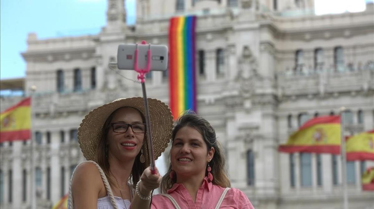 Dos turistas se hacen un 'selfie' frente al Ayuntamiento de Madrid, que luce la bandera del arcoiris en homenaje al World Pride 2017.