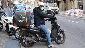 Un mensajero de Stuart inicia un reparto con su motocicleta, en Barcelona.
