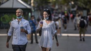 Dos viandantes por las Ramblas durante la ola de calor de 2020.