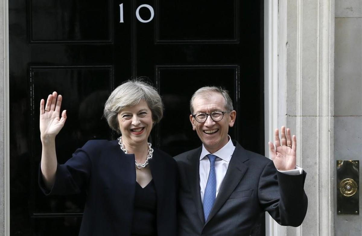 Theresa May y su esposo, Philip May, saludan en la entrada del número 10 de Downing Street, este miércoles, en Londres.