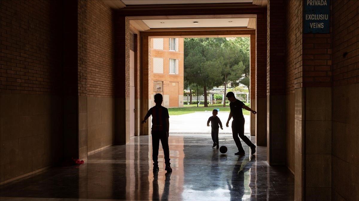 Unos niños juegan a fútbol en una zona privada de una comunidad de vecinos de Barcelona.