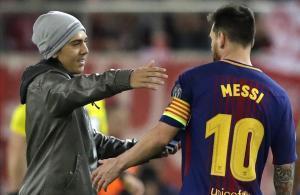 Un fan que saltó al campo se dispone a abrazar a Messi durante el partido de este martes.