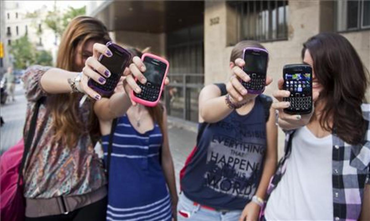 Unas adolescentes muestran sus teléfonos móviles a la puerta de su instituto en Barcelona.