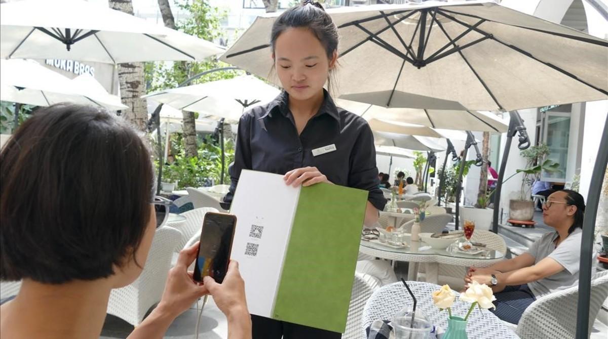 Una joven paga su consumición en un terraza de Shanghái con el teléfono móvil.