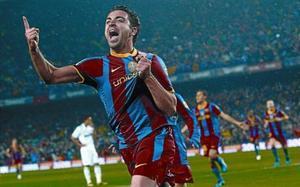 Xavi celebra el gol que consiguió ante el Madrid agarrándose el escudo de la camiseta.