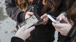 Varios jóvenes usando sus móviles.