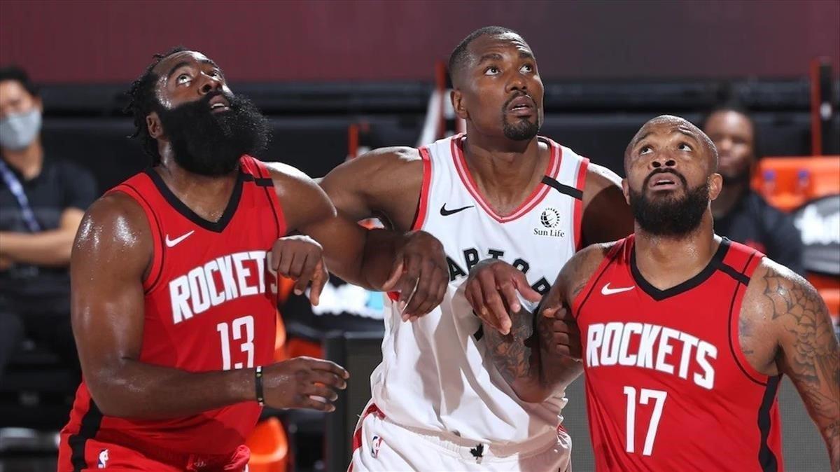 Serge Ibaka,jugadornacionalizado de los Raptors, vigente campeones, pugna con Harden y Pj. Tucker, de los Rockets