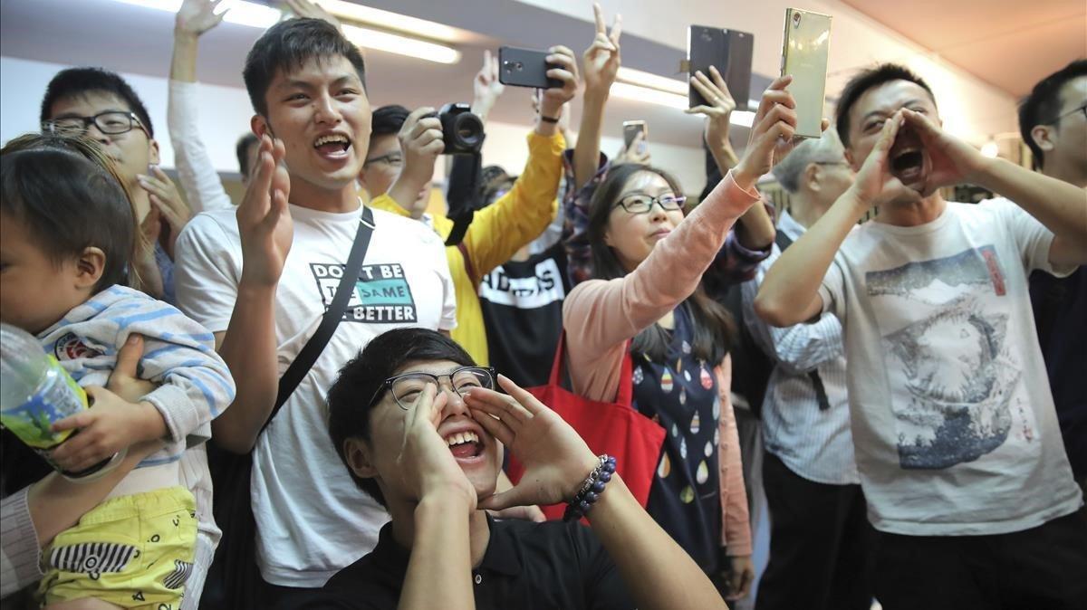 Jóvenes antigubernamentales celebran el resultado de las elecciones en Hong Kong, este domingo.