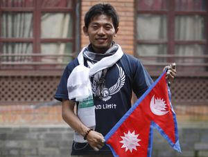 FILE- In this Aug. 23, 2015 file photo, Japanese climber Nobukazu Kuriki poses with a Nepalese flag during a press conference as he attempts to be the first to scale Mount Everest since the April 2015 earthquake that killed 19 mountaineers, in Kathmandu, Nepal. Kuriki and another foreign climber attempting to scale Mount Everest have died on the world's highest peak, a Nepal mountaineering official said Monday, May 21, 2018. (AP Photo/Bikram Rai, File)