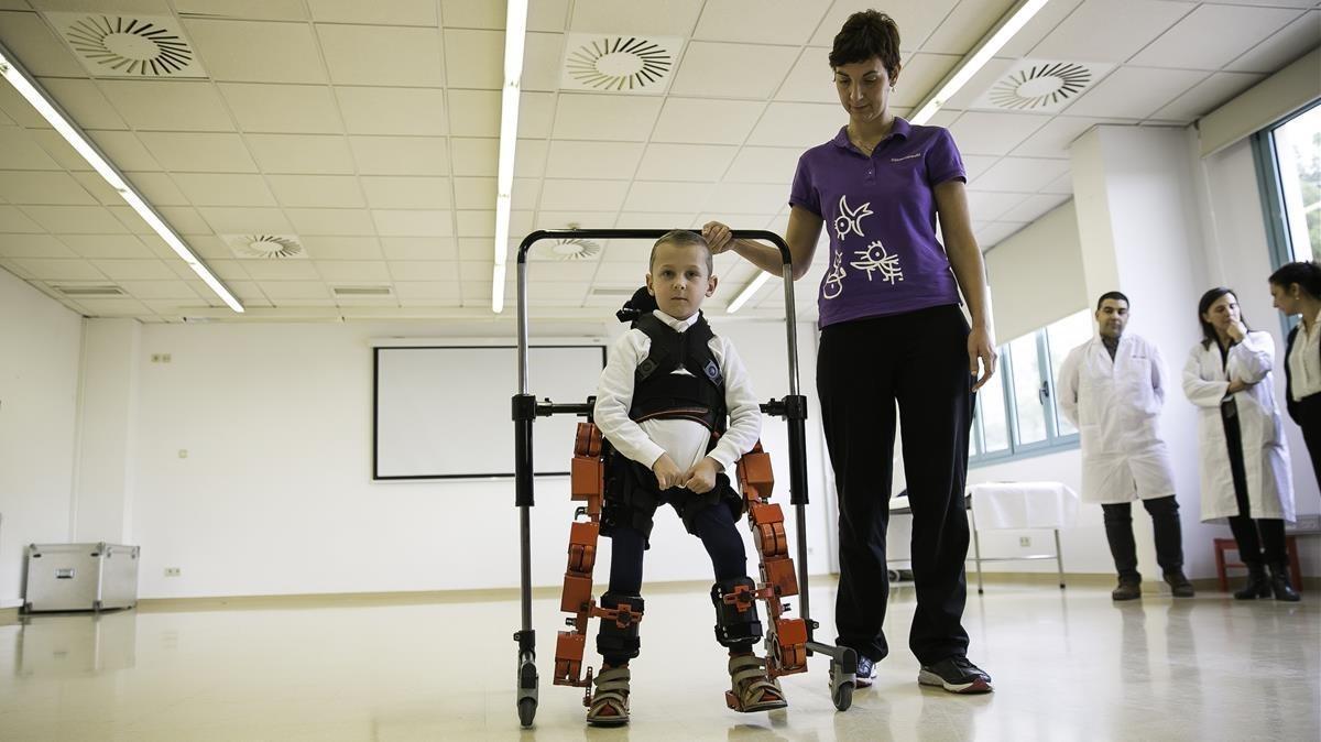 Una fisioterapeuta del Hospital Sant Joan de Déu ayuda al pequeño Jens, con atrofia muscular espinal, con el exoesqueleto.