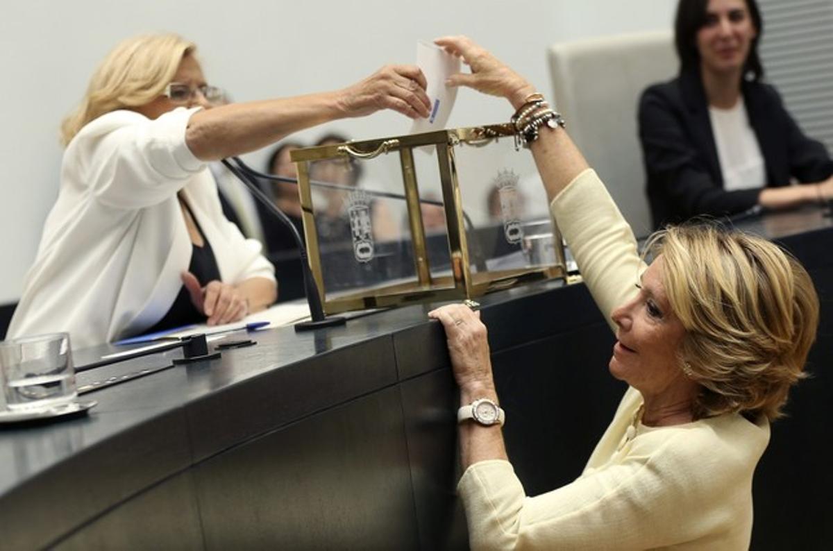 Manuela Carmena ayuda a votar a Esperanza Aguirre, durante la votación de investidura, el sábado en el Ayuntamiento de Madrid.