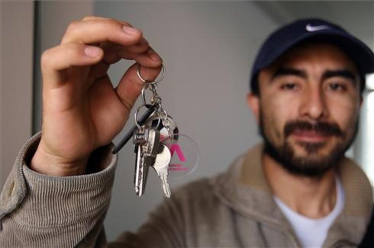 Un joven enseña las llaves de su piso de alquiler en Barcelona.