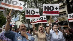 Manifestantes contrarios a Maduro sostienen pancartas en las que reclaman que se acabe la dictadura en Venezuela.