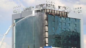 Los bomberos extinguen las llamas del aparatoso en la fachada exterior del Hotel Nuevo Madrid, situado junto a la zona norte de la M-30 en Madrid, este jueves.