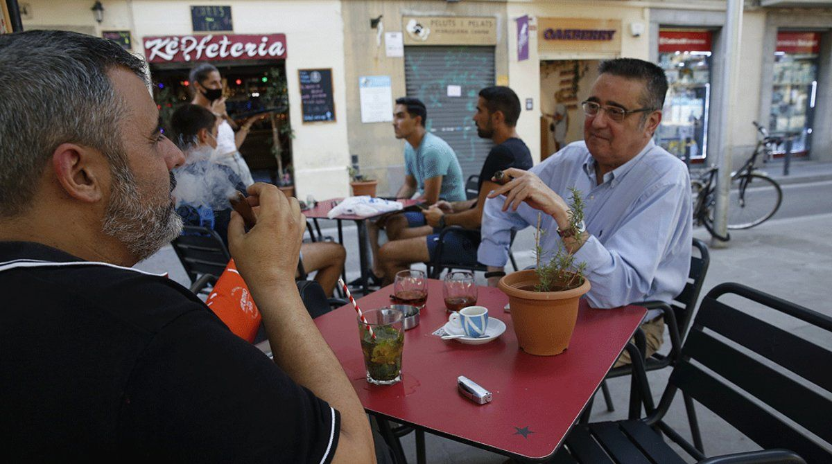 Dos hombres fuman sendos puros en una terraza de Barcelona, sin respetar la distancia de seguridad, este viernes 14 de agosto.