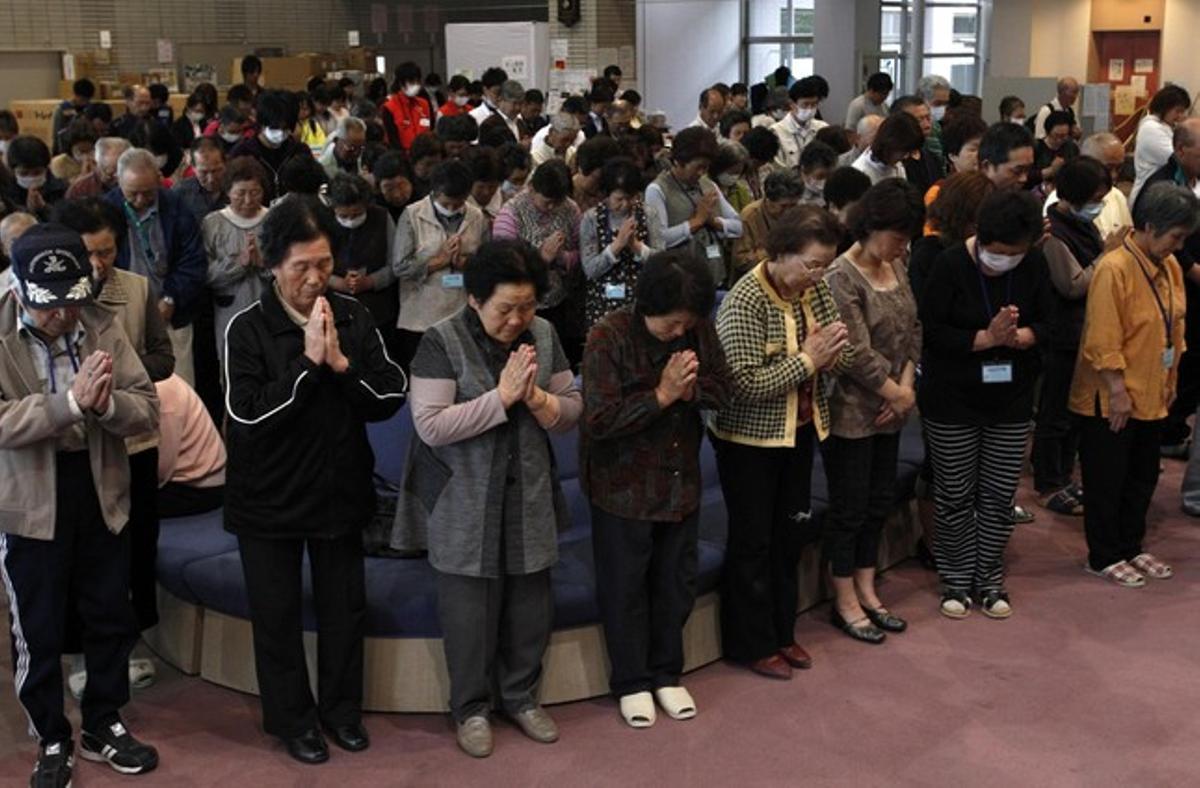 Evacuados de la prefectura de Fukushima guardan un minuto de silencio por las víctimas del terrremoto.