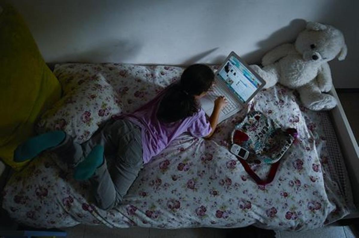Una menor consulta Facebook mediante un ordenador portátil en su cuarto.