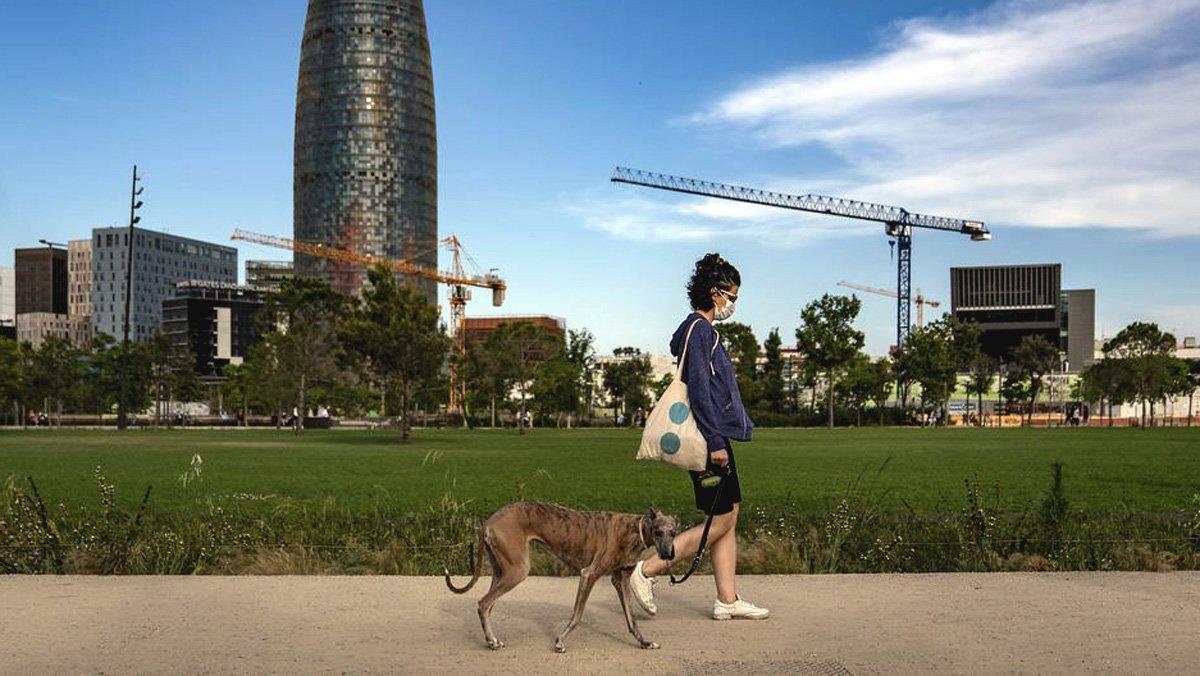 Una mujer pasea el perro por un parque de Barcelona.