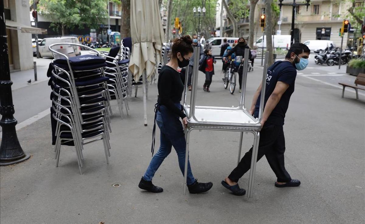 Trabajadores de un restaurante de la rambla del Poblenou, en Barcelona, recogen las mesas de la terraza a las cinco de la tarde.
