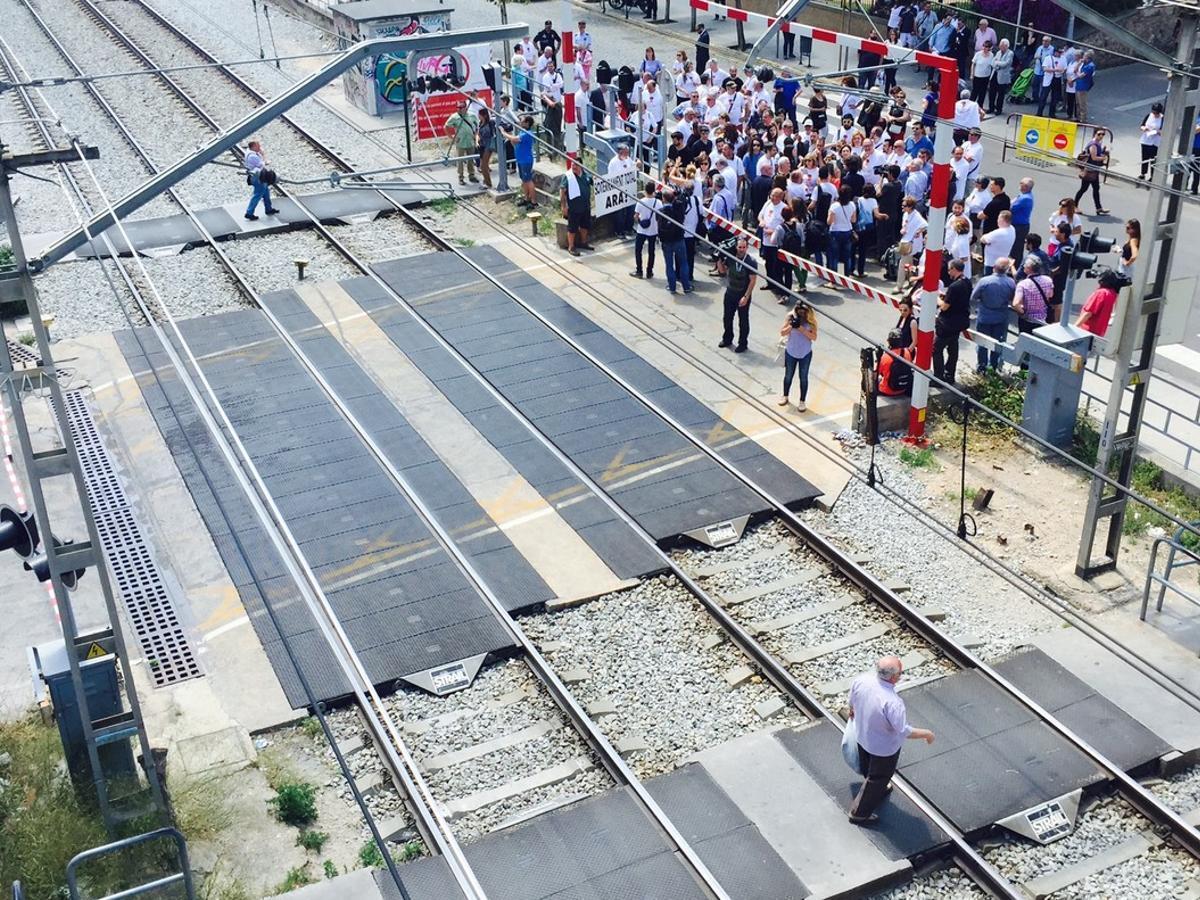 Dos vecinos de Sant Feliu cruzan el paso a nivel, cerrado, ante la mirada de vecinos y autoridades.