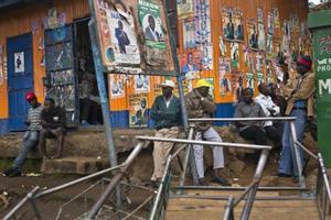 Un grupo de kenianosjunto a un local con la fachada cubierta de carteles durante la campaña electoral.