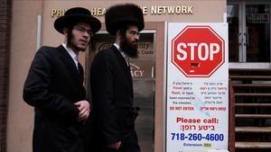 Dos hombres pasan ante un cartel informativo sobre el brote de sarampión en Brooklyn, Nueva York.